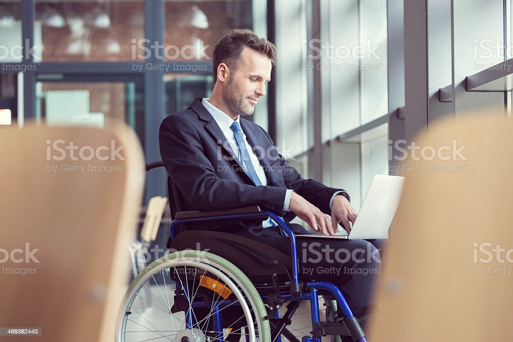 Disabled businessman working in an office Disabled businessman wearing suit sitting in a wheelchair in an office and working on laptop. 2015 Stock Photo