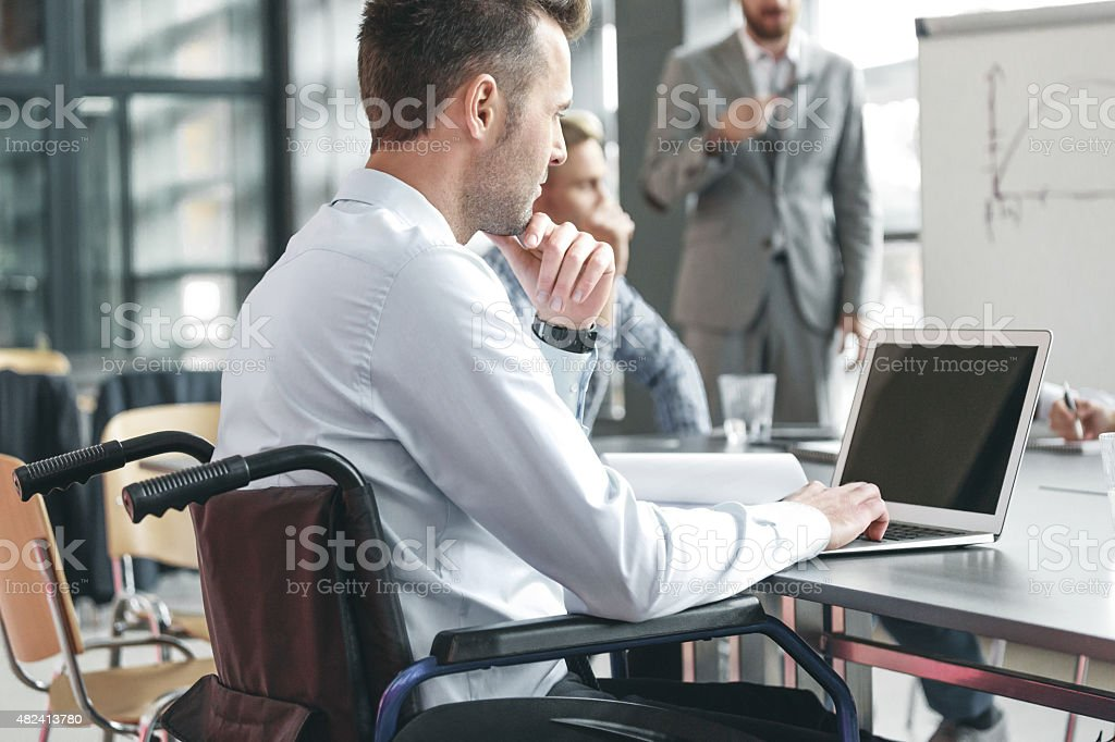 Disabled businessman working in an office Disabled businessman wearing shirt and tie sitting in a wheelchair at the conference table in a board room in an office, working on laptop. In the background blured man standing next to flipchart. 2015 Stock Photo
