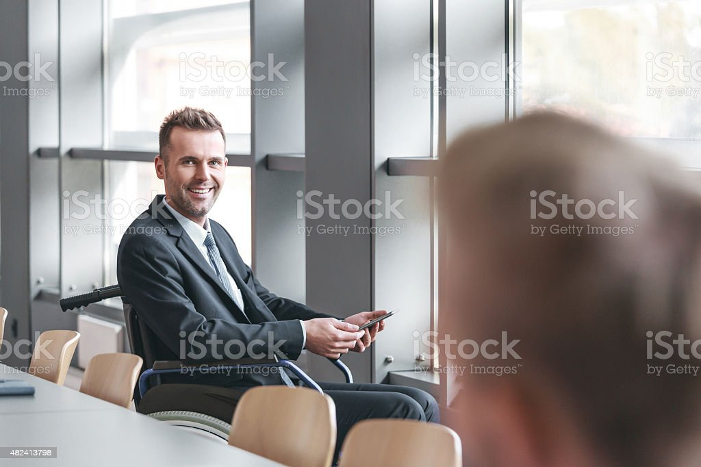 Disabled businessman working in an office Disabled businessman wearing suit sitting in a wheelchair in an office, smiling at camera. 2015 Stock Photo