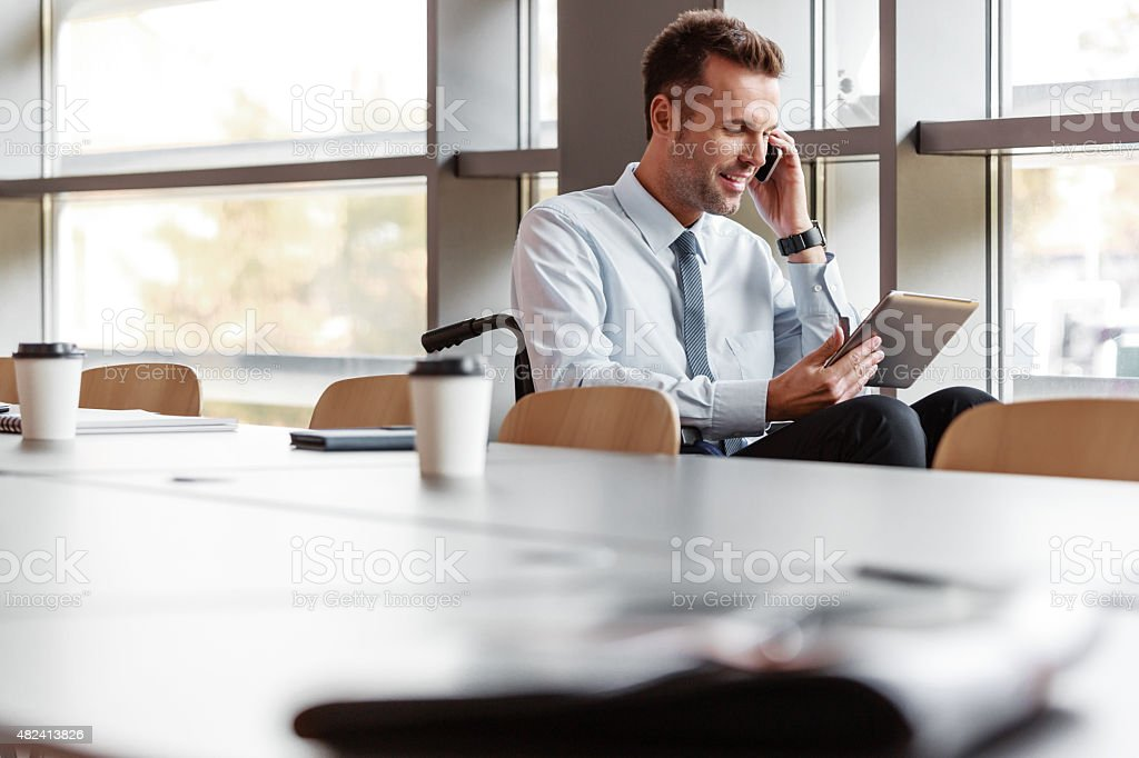 Disabled businessman working in an office Disabled businessman wearing shirt and tie sitting in a wheelchair in an office, holding a digital tablet in hand and talking on phone.  2015 Stock Photo