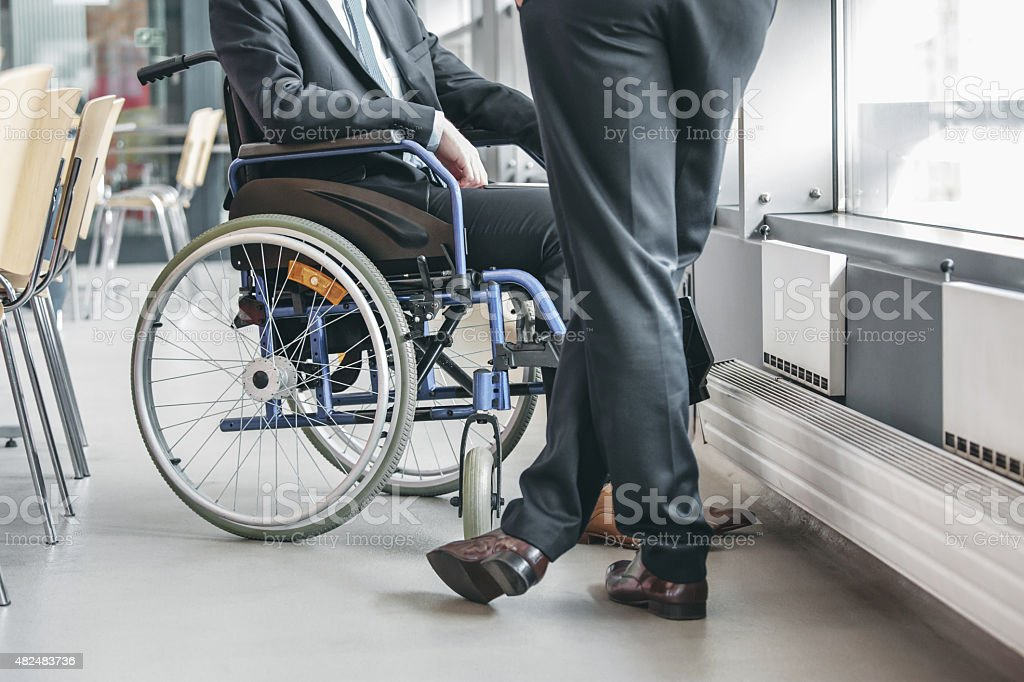 Disabled businessman working in an office Disabled businessman wearing suit sitting in a wheelchair in an office and talking with his colleague. Close up of legs and wheelchair. Unrecognizable people.  2015 Stock Photo