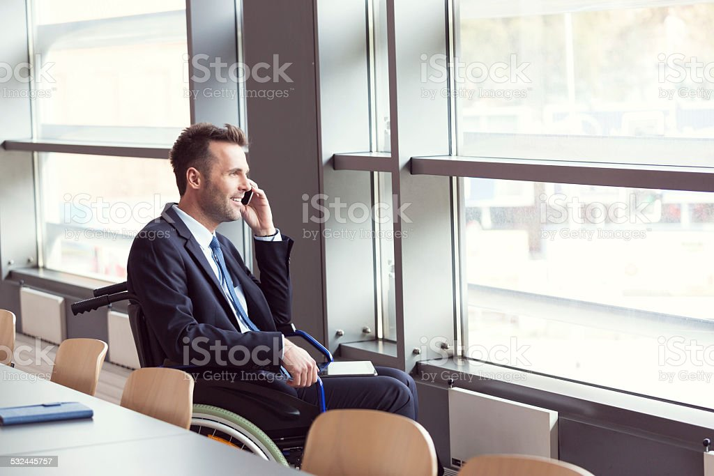 Disabled businessman working in an office Disabled businessman sitting in a wheelchair in an office, looking out the window and talking on cell phone. 2015 Stock Photo