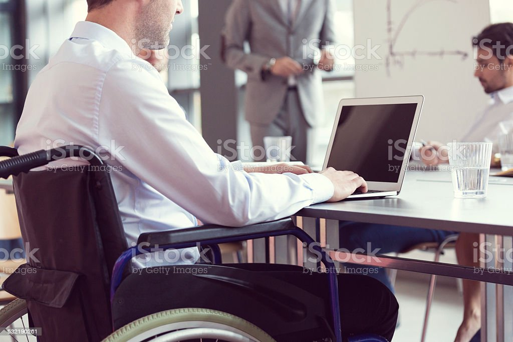 Disabled businessman working on laptop in an office stock photo
