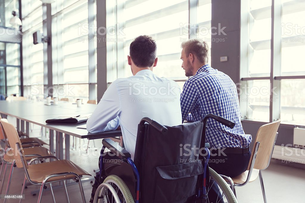 Disabled businessman working with his colleague in an office Disabled businessman sitting in a wheelchair at the conference table in board room in an office and working with his colleague together. Back view. 2015 Stock Photo