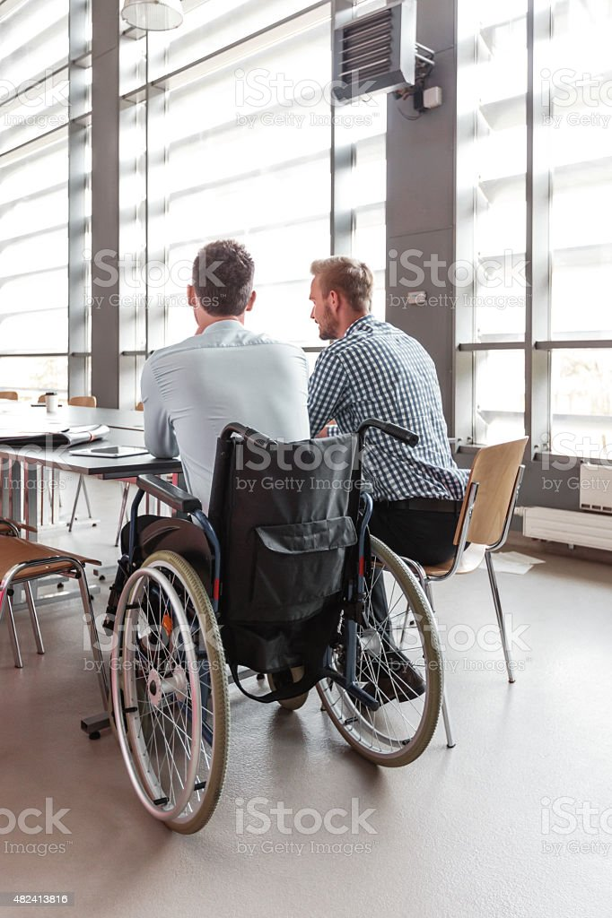 Disabled businessman working with his colleague in an office Back view of disabled businessman sitting in a wheelchair at the office table in an office and collaborating with his colleague.  2015 Stock Photo