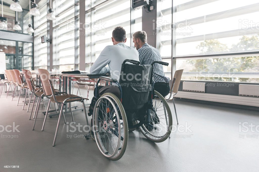 Disabled businessman working with his colleague in an office stock photo