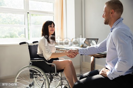1144373653 istock photo Disabled Businesswoman Shaking Hand With Her Partner 975124376