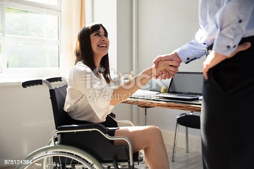 1144373653 istock photo Disabled Businesswoman Shaking Hand With Her Partner 975124384