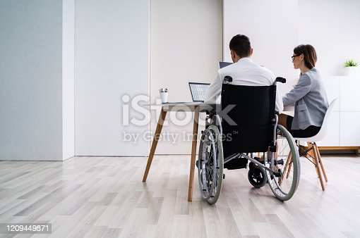 1144373653 istock photo Disabled Businesswoman Sitting With Her Partner In Office 1209449871
