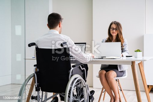 1144373653 istock photo Disabled Businesswoman Sitting With Her Partner In Office 1209449882