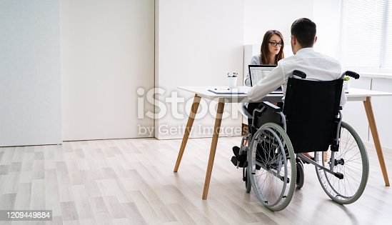 1144373653 istock photo Disabled Businesswoman Sitting With Her Partner In Office 1209449884