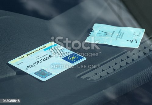 istock Disabled car parking badge being displayed in the front of a car windscreen 945085848