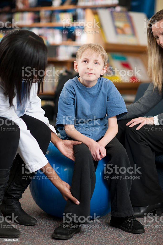 A mother and physical therapist are helping a child with a physical...