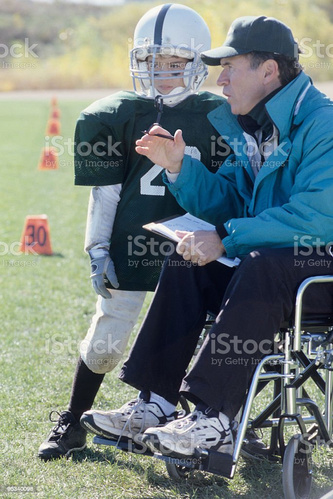 A disabled coach leads his junior football team  royalty-free stock photo