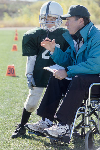 A disabled coach leads his junior football team  stock photo