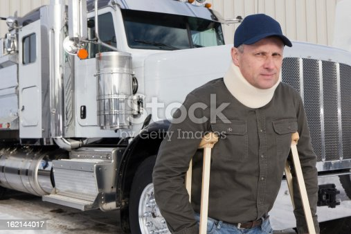 A royalty free image from the trucking industry of a truck driver on crutches.