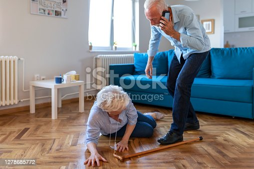 Senior wife sitting on floor while retired husband talking on smartphone calling an ambulance