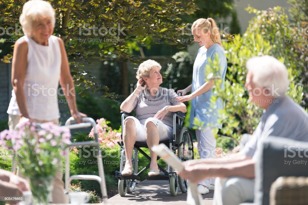 Disabled elderly woman in garden stock photo