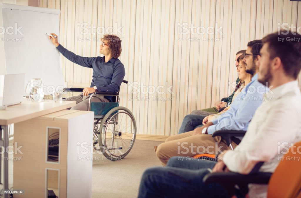 Disabled employee near flip chart, having presentation in front of the coworkers royaltyfri bildbanksbilder
