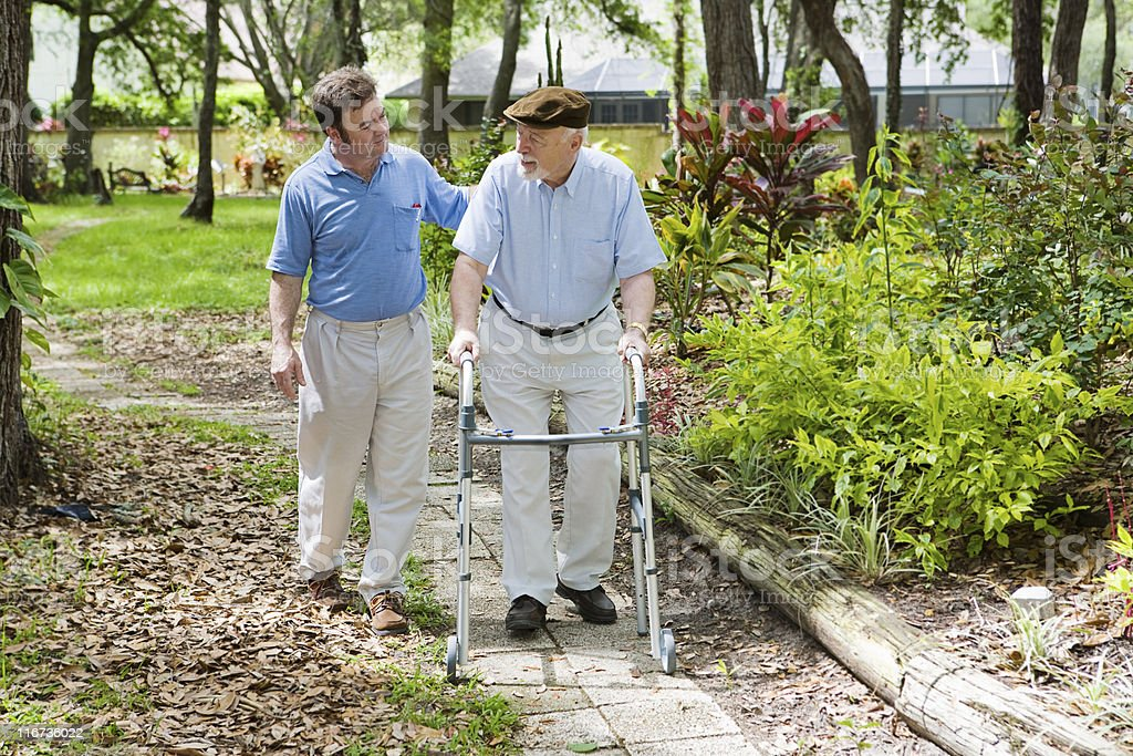 Disabled father and son taking an afternoon walk in park  stock photo