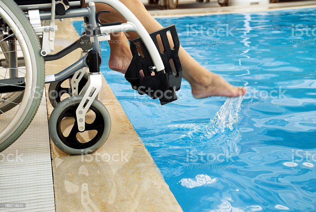 Disabled female by a swimming pool royalty-free stock photo