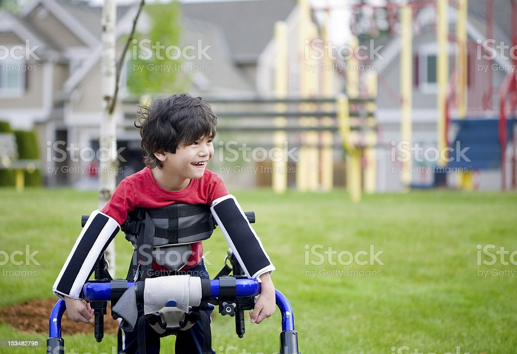 Disabled four year old boy standing in walker by playground stock photo