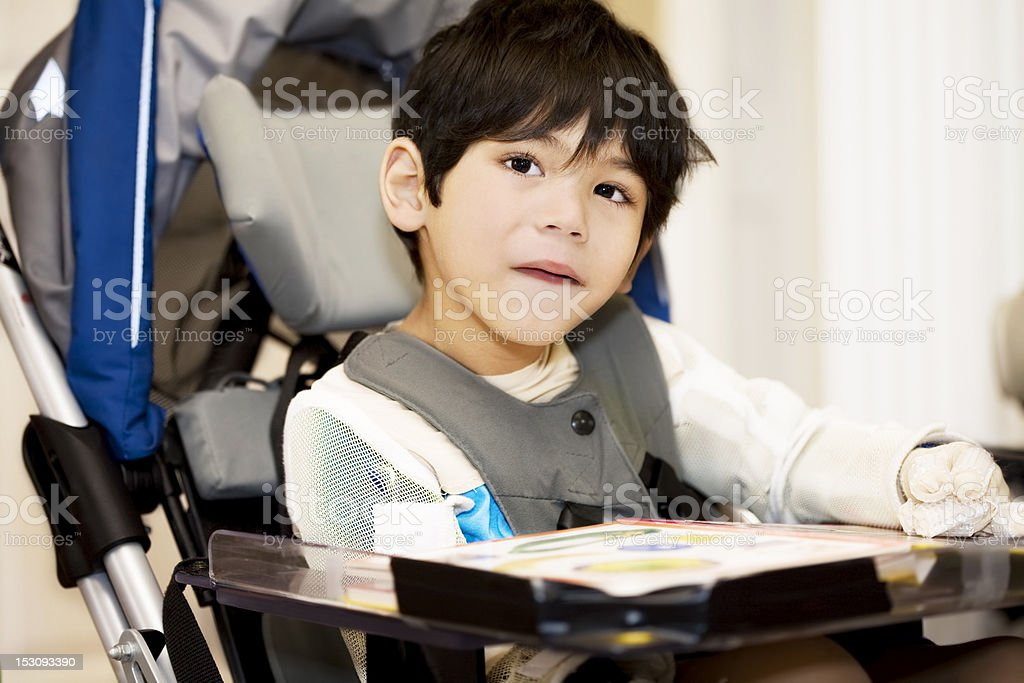 Disabled four year old boy studying or reading in wheelchair stock photo