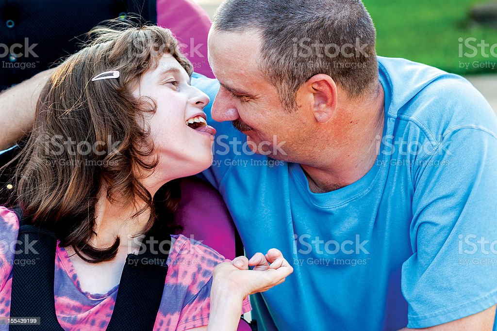 Disabled girl giving Daddy a kiss stock photo