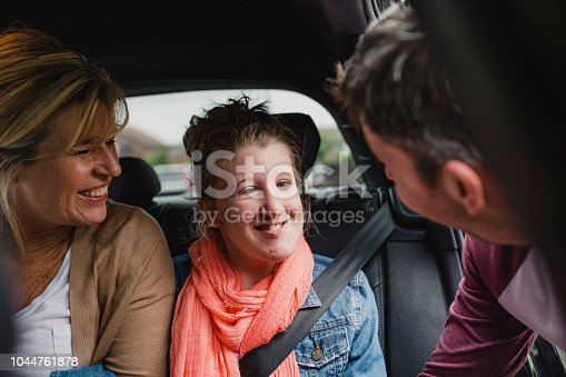 Happy disabled teenager is getting in to the car with her parents.