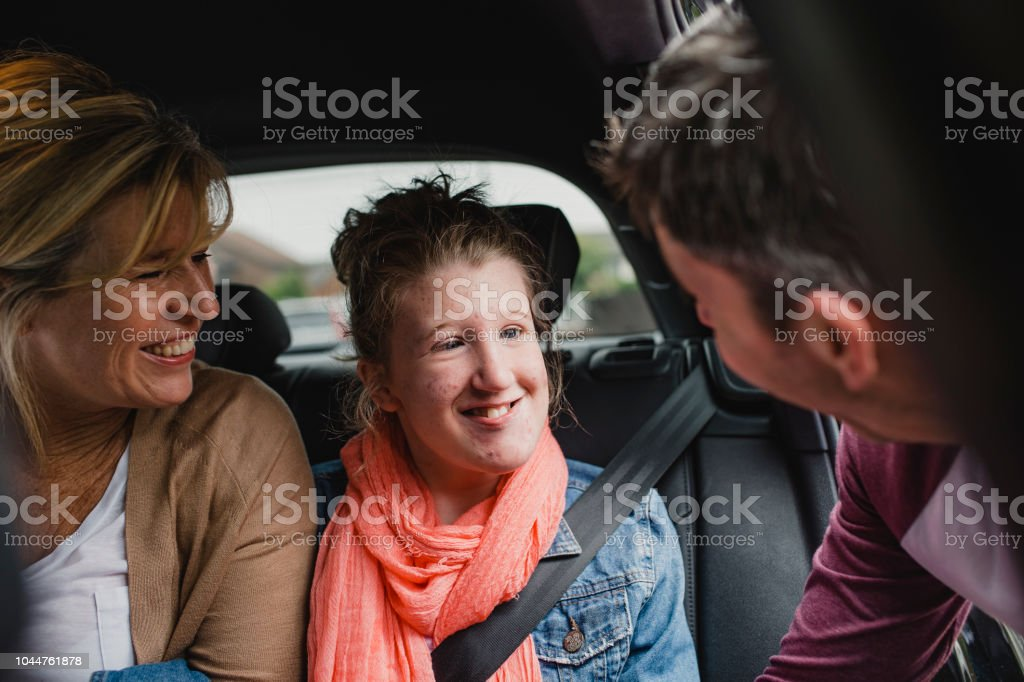 Disabled Girl in the Car with Parents stock photo