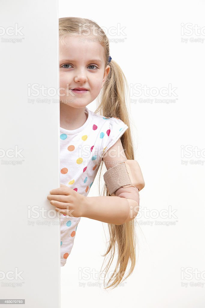 Disabled Girl Looking Around White Wall In Studio stock photo