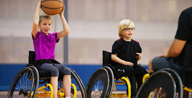 disabled girl passing a basketball - wheelchair sports stock photos and pictures
