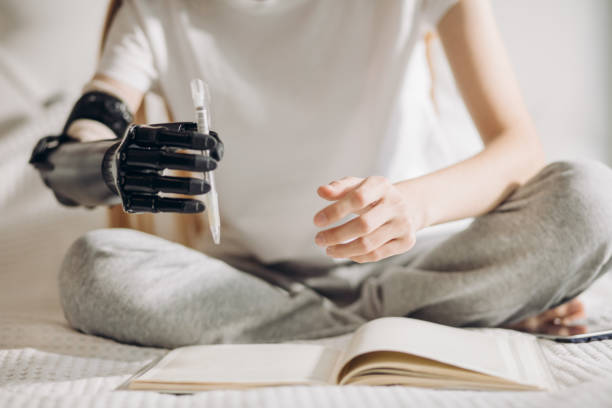 障害のある女の子は人工腕でペンを保持しようとします - 四肢 ストックフォトと画像
