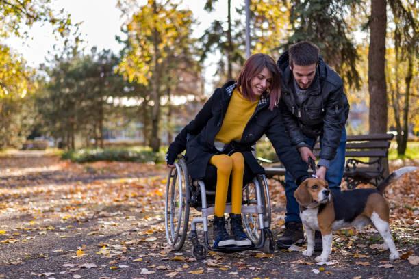 公園で犬と遊ぶボーイフレンドと障害のある女の子 - disabilitycollection ストックフォトと画像