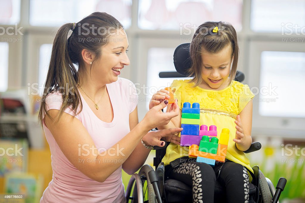 A caregiver is sitting with a cute little girl that has cerebral...
