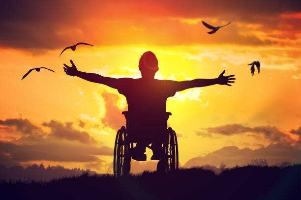 Disabled handicapped man has a hope. He is sitting on wheelchair and stretching hands at sunset. stock photo
