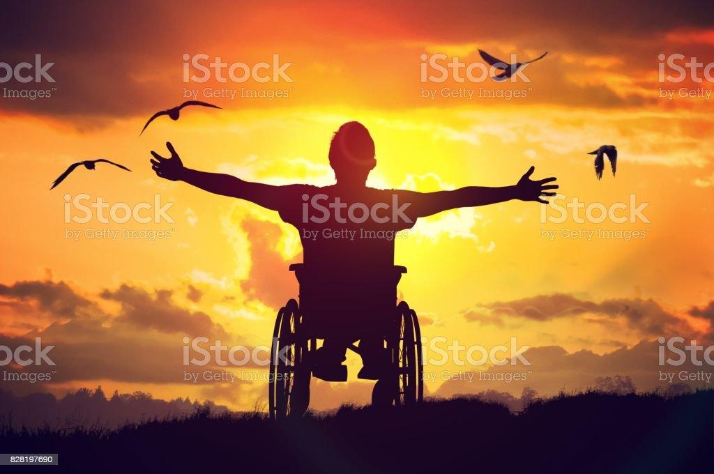Behinderte, behinderte Mensch hat eine Hoffnung. Er sitzt im Rollstuhl und Dehnung Hände bei Sonnenuntergang. – Foto