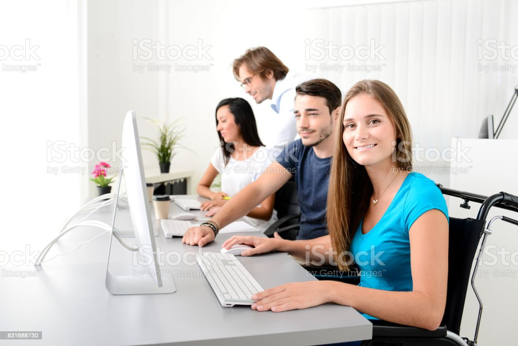 disabled handicapped young female worker on wheelchair with coworker in business office working on a desktop computer stock photo