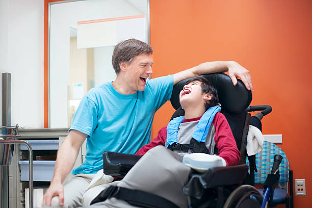 Disabled little boy in wheelchair talking with father in hospital room stock photo