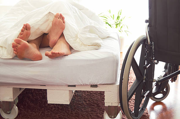 Disabled man having sex in bed with his partner. stock photo