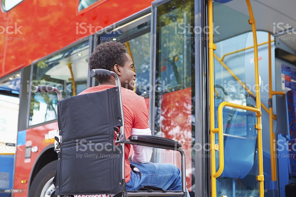 Disabled Man In Wheelchair Boarding Bus stock photo