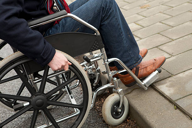 Disabled man in wheelchair needs help, fatality Man in wheelchair after acident at work. Worker suffering from an illness.  If you want more images with a man in wheelchair please click here. discriminatory stock pictures, royalty-free photos & images