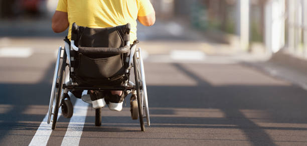 Disabled man in wheelchair Disabled man in wheelchair on road paraplegic stock pictures, royalty-free photos & images