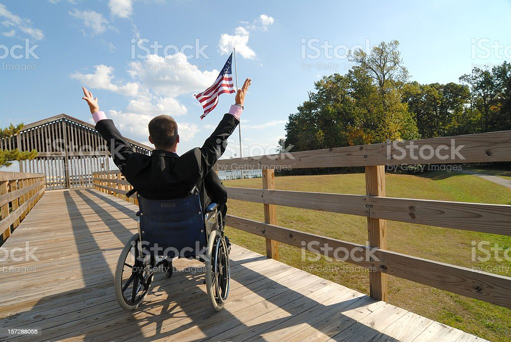 Disabled Man in Wheelchair Raises Arms toward American Flag royalty-free stock photo