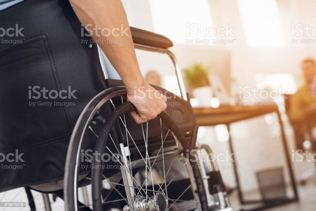 A disabled man is sitting in a wheelchair. stock photo