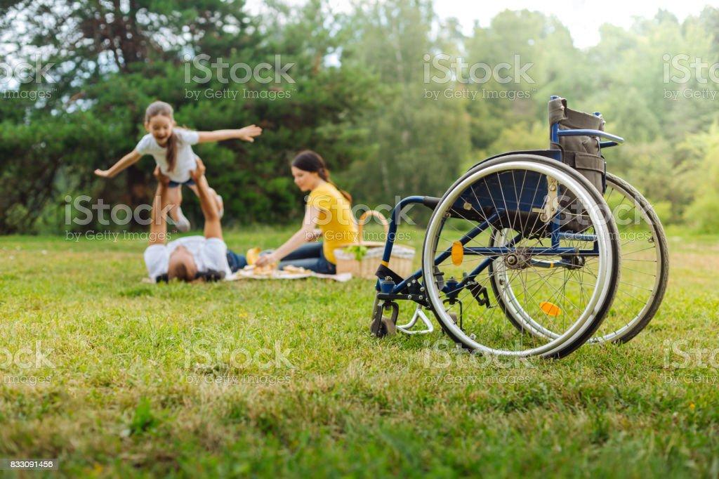 Hombre discapacitado levantando a su hija en picnic - foto de stock