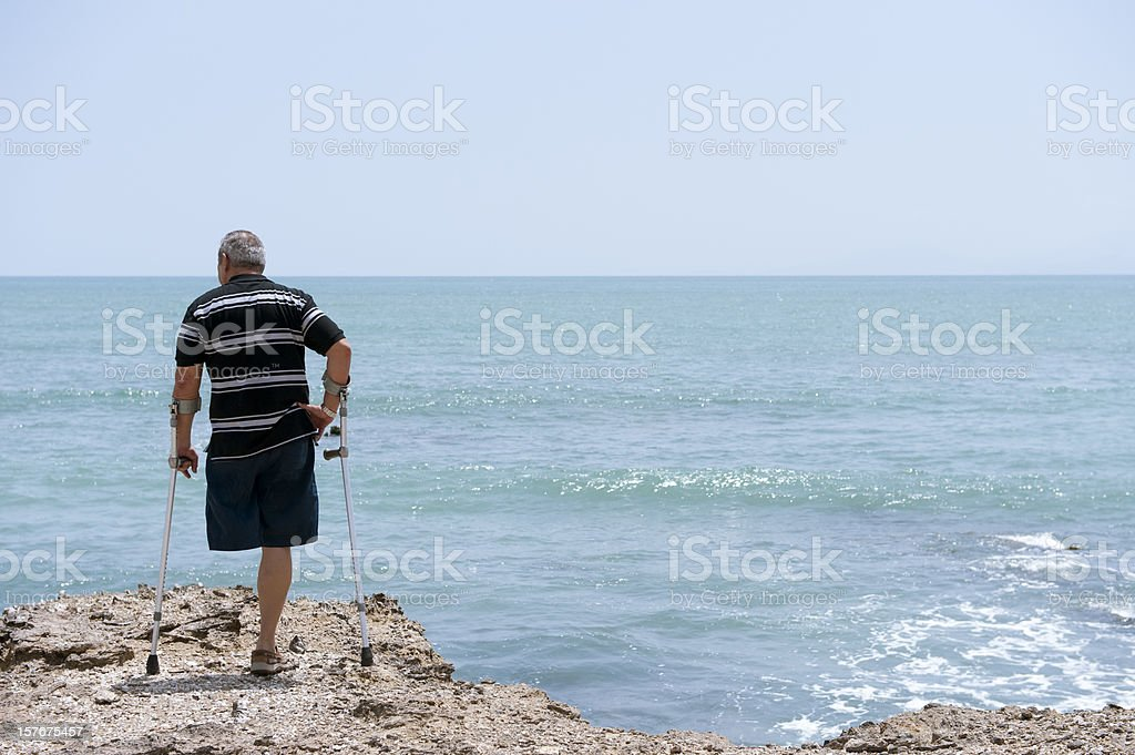 Disabled man on crutches on rocks at the sea stock photo