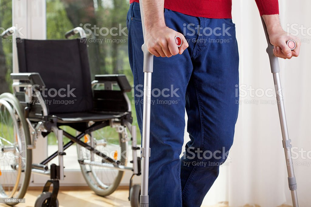Disabled man on crutches stock photo