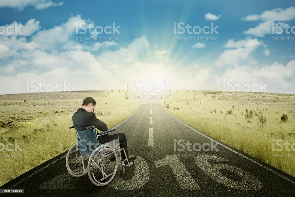 Disabled man on the road with numbers 2016 stock photo