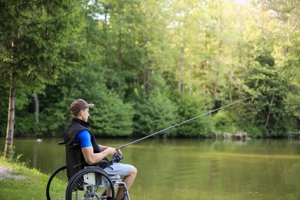 Disabled man on wheelchair fishing at lake stock photo
